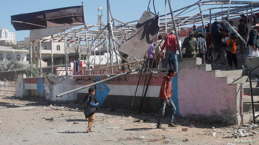 People gather at the scene of a blast which struck a military graduation parade in the town of al-Dhalea, Yemen December 29,…