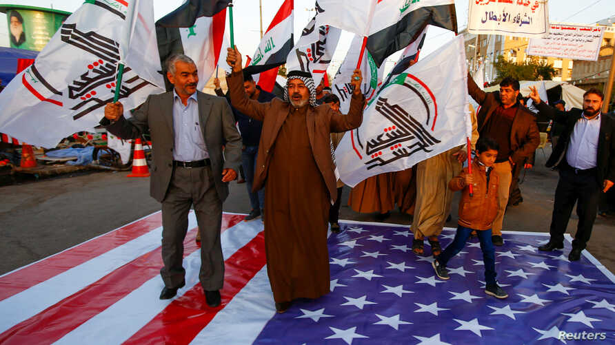 Iraqi people walk on a U.S. flag in a protest after an airstrike at the headquarters of Kataib Hezbollah militia group in Qaim,…
