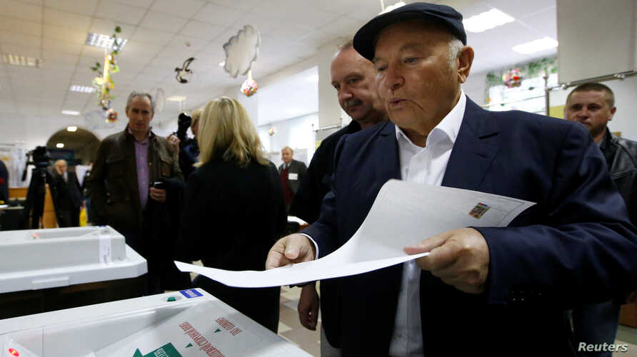 Former mayor of Moscow Yuri Luzhkov casts his ballot at a polling station during a parliamentary election in Moscow, Russia,…