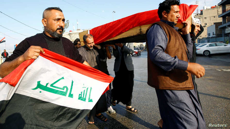Mourners carry the coffin of a demonstrator who was killed at an anti-government protest in Nassiriya, during a funeral in…