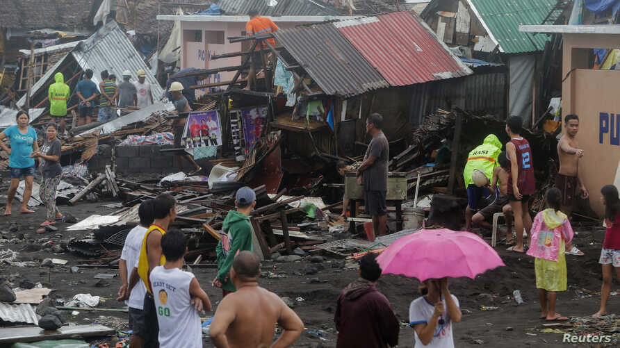 Residents stand among their damaged houses after Typhoon Kammuri hit Legazpi City, Albay, Philippines, December 2, 2019…