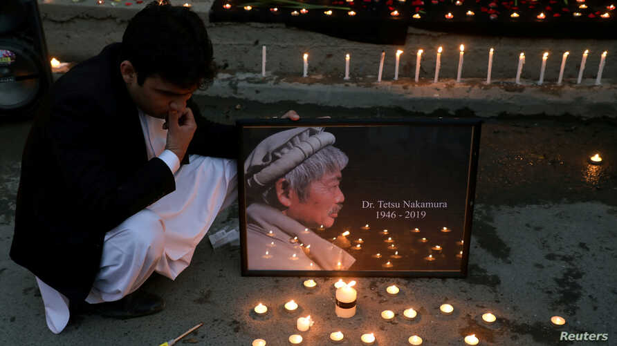 Afghan men light candles for Japanese doctor Tetsu Nakamura, who was killed in Jalalabad in yesterday's attack, in Kabul,…