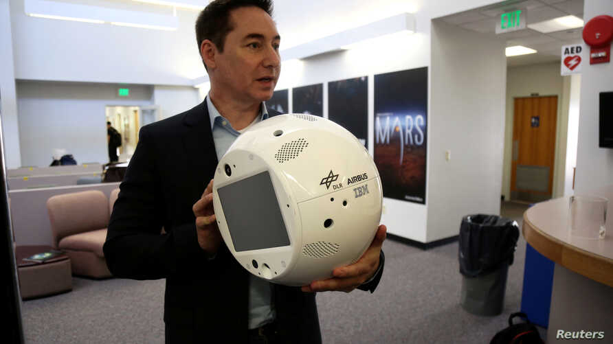 FILE PHOTO: Bret Greenstein, IBM Global Vice President of Watson Internet of Things Offerings, holds a clone of an artificial…