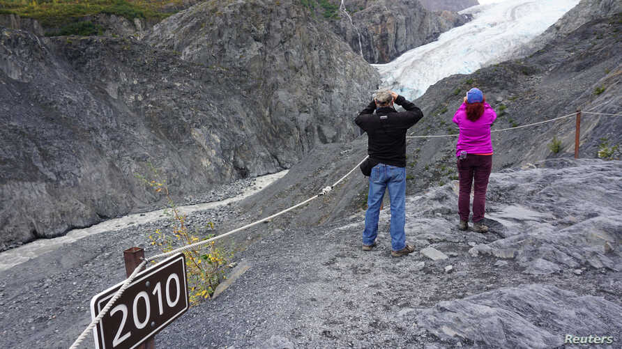 A sign marks where the end of the Exit glacier was in 2010 near tourists taking photos in the Kenai Fjords National Park,…