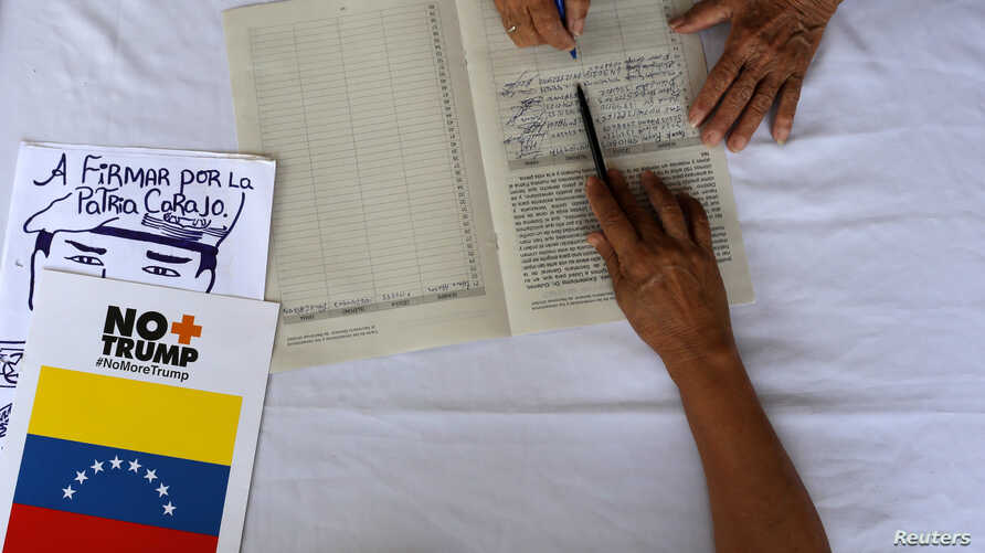 A supporter of Venezuela's President Nicolas Maduro signs a petition against the U.S. sanctions on Venezuela during a gathering…
