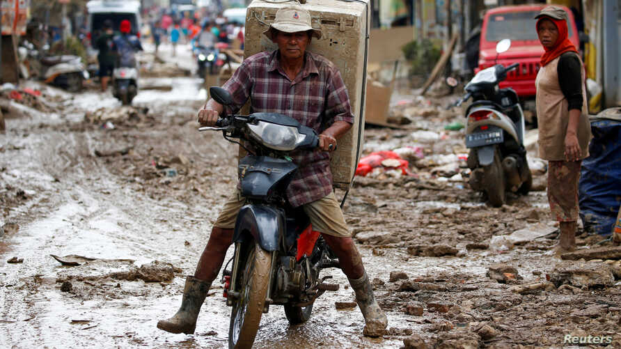 Man carrying a washing machine rides a motorbike as he collects items at a residential area affected by floods in Bekasi, West…