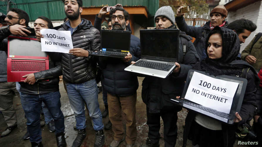 FILE PHOTO: Kashmiri journalists display laptops and placards during a protest demanding restoration of internet service, in…