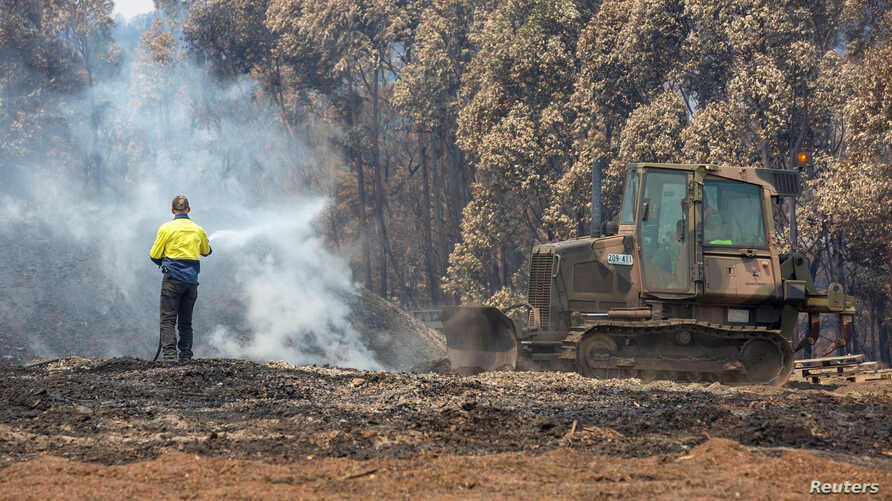 An Australian Army combat engineer from the 5th Engineer Regiment utilises a JD-450 Bulldozer to spread out burnt woodchip at…