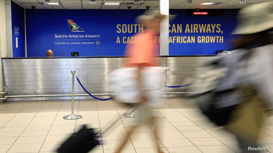 Passengers walk past a South African Airways (SAA) customer desk at the O.R. Tambo International Airport in Johannesburg, South…