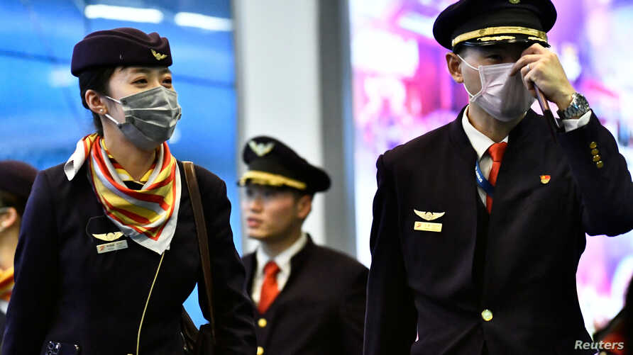 A flight crew, wearing masks, arrives on a direct flight from China, after Canada's Public Health Agency added a screening…