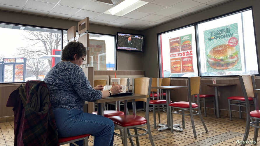 A woman eats in a fast food restaurant as a television shows live coverage of U.S. President Donald Trump's U.S. Senate…