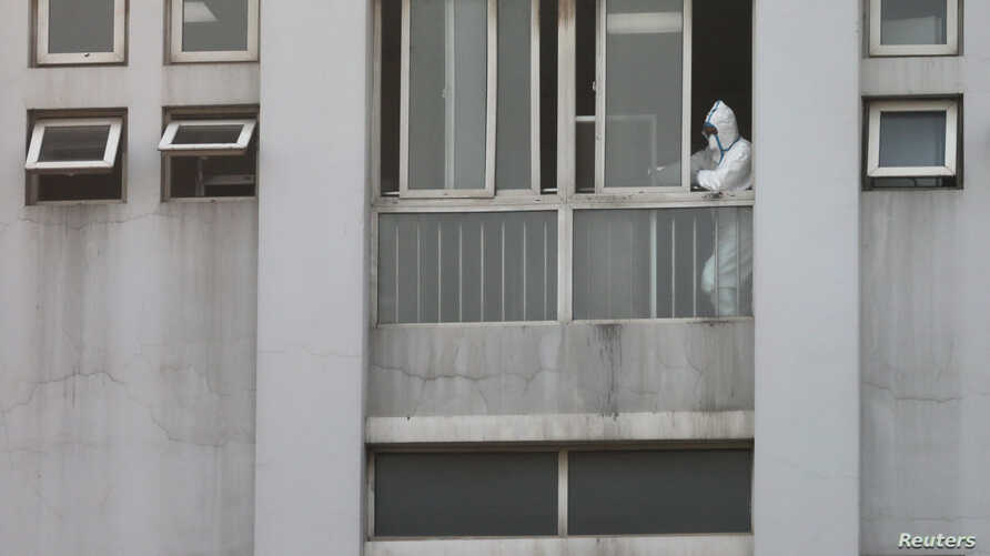 FILE PHOTO: A medical staff member is seen by a window at the Jinyintan hospital, where the patients with pneumonia caused by…