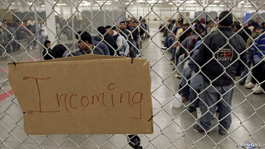 Undocumented immigrants wait in a holding facility after arriving at the U.S. Border Patrol detention center in Nogales,…