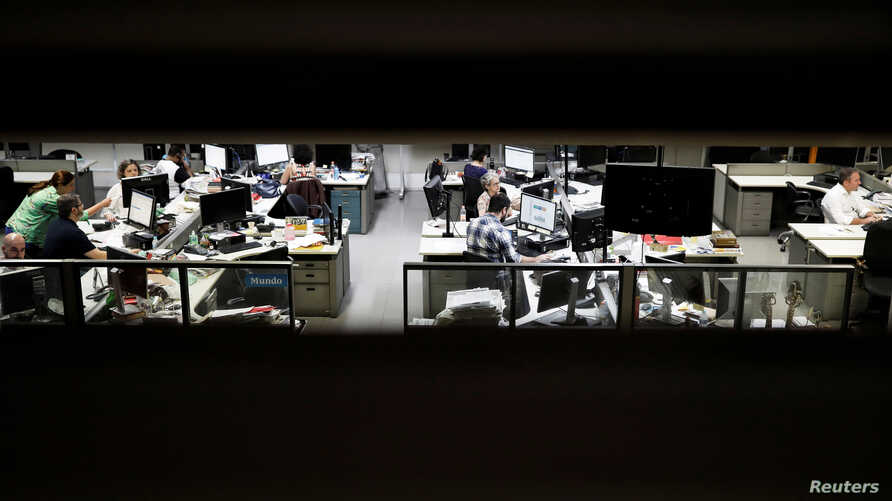FILE - Journalists of Folha de S. Paulo newspaper work inside the editorial office of the newspaper in Sao Paulo, Brazil, Oct. 31, 2018.