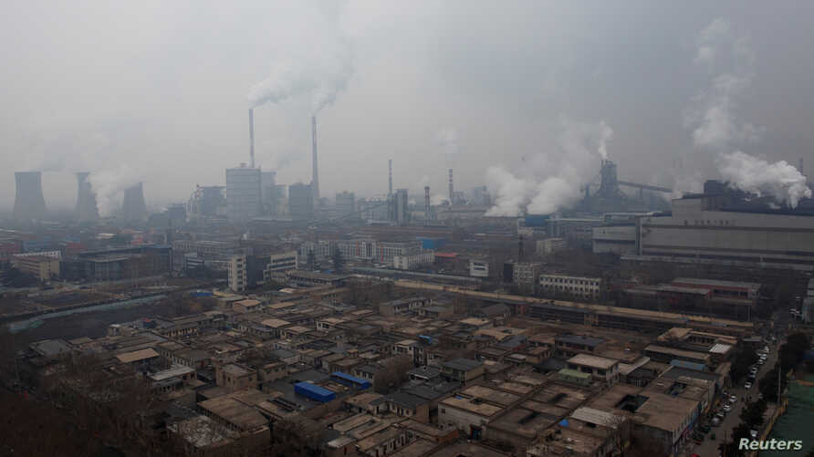 Smoke stacks and cooling towers of a power plant rise above a low-rise neighborhood that borders a steel plant in Anyang, Henan…