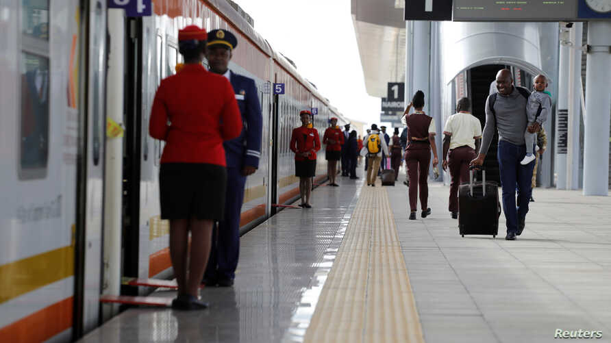 A man carries an infant as he walks along the platform in front an SGR train traveling to Mombasa from the Nairobi SGR Terminus…