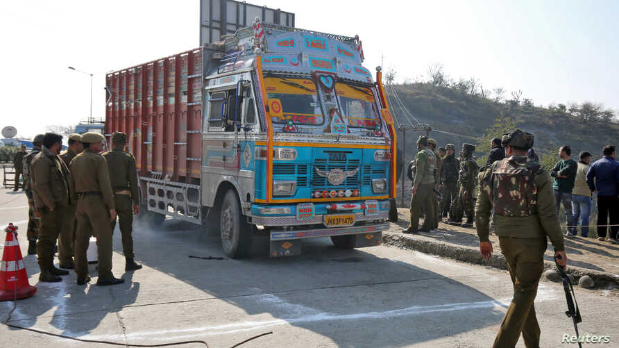 Indian security forces stand around a truck which was used by suspected militants, at the site of a gun battle at Nagrota, on…