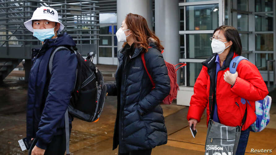 FILE PHOTO: Passengers wearing masks, amid the health threat of novel coronavirus, arrive on a direct flight from China at…