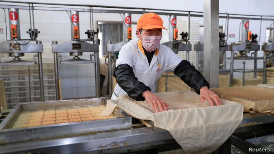 A worker wearing a face mask works on a production line manufacturing soybean-based food products at a factory in Hefei, Anhui…