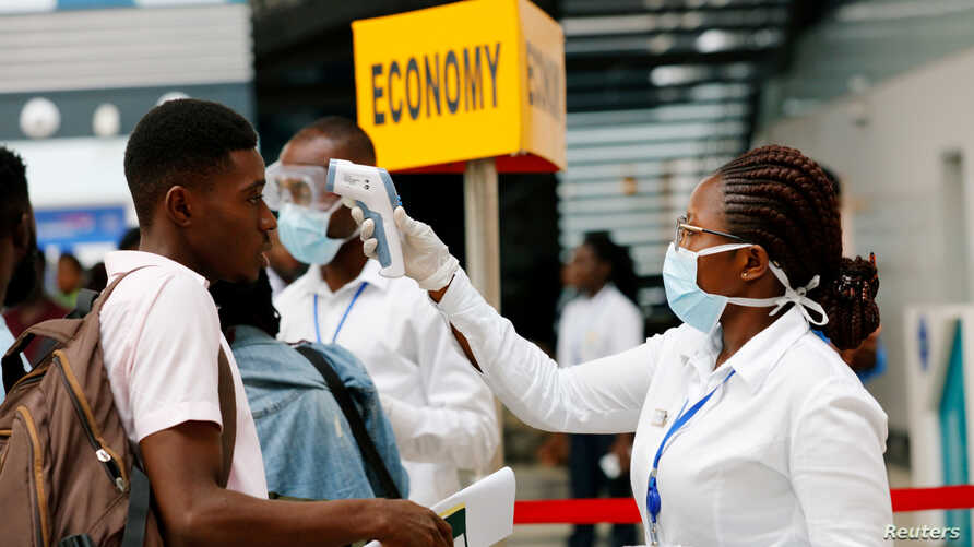 FILE PHOTO: A health worker checks the temperature of a traveller as part of the coronavirus screening procedure at the Kotoka…