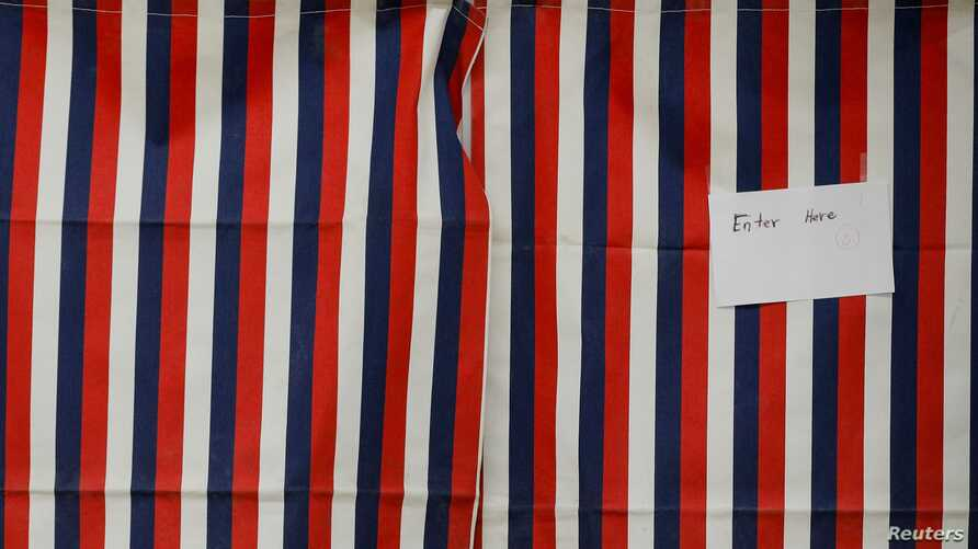 A voter fills out a ballot inside a voting booth for New Hampshire's first-in-the-nation U.S. presidential primary election at…