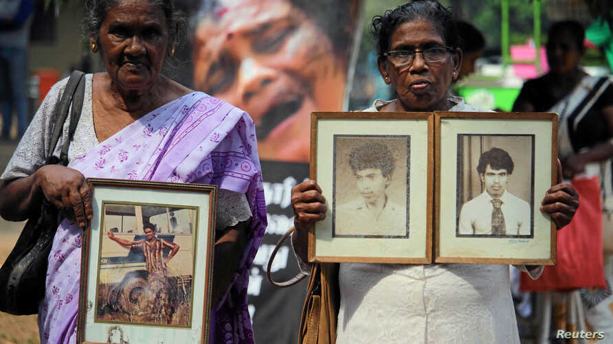 Women hold the portraits of their relatives, who disappeared at a protest, as they demand an investigation for those who went…