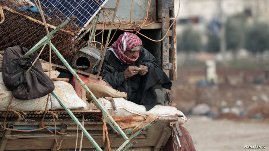 An internally displaced man, who fled from Idlib, rolls a cigarette as he rides on a pick up truck with belongings in Azaz,…