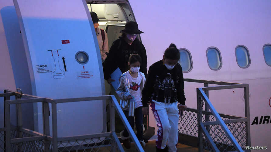 Australian evacuees who were quarantined on Christmas Island over concerns about the coronavirus disembark from a plane at…
