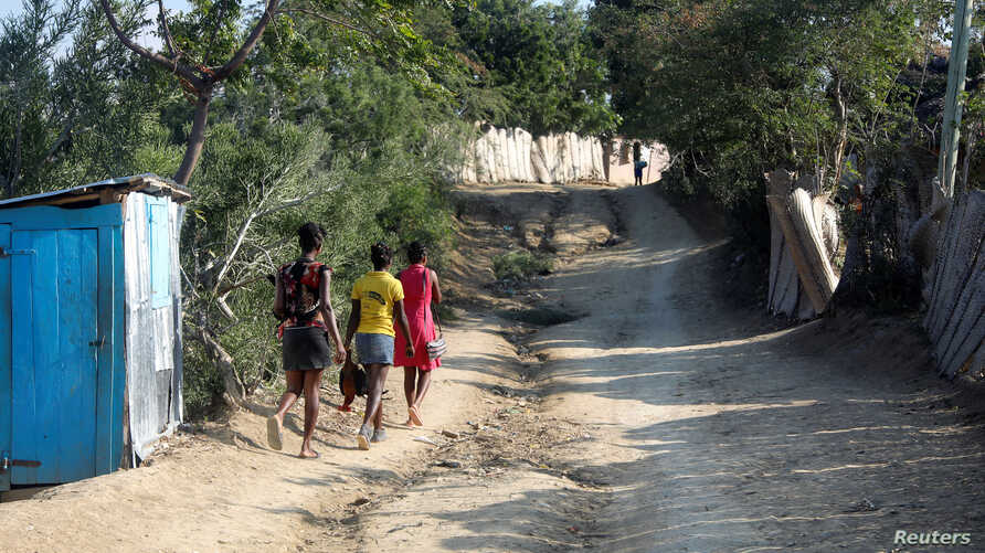 Girls carry roosters down a dirt road in Jean-Rabel, Haiti January 31, 2020. Picture taken January 31, 2020. REUTERS/Valerie…