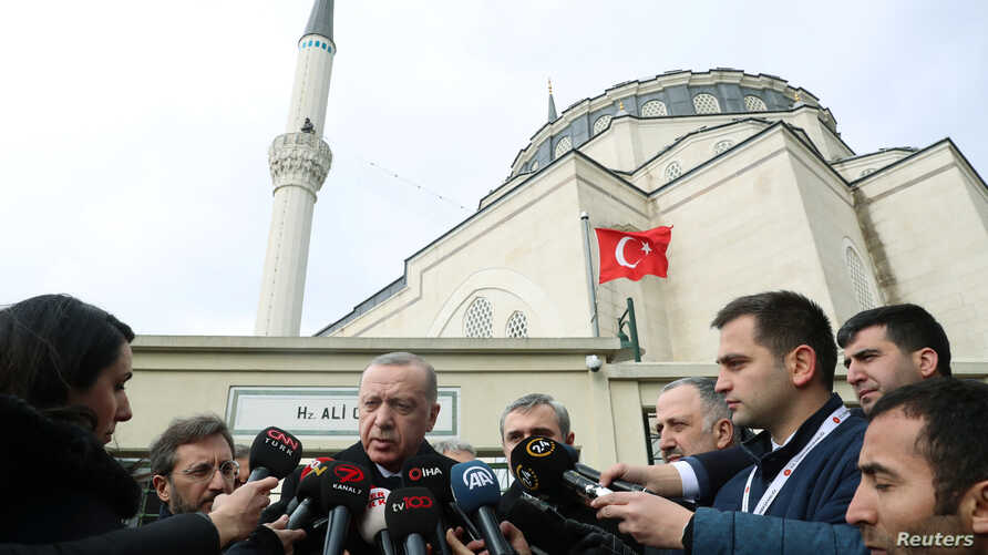 Turkish President Tayyip Erdogan talks to journalists in front of a mosque as he leaves friday prayers in Istanbul, Turkey,…