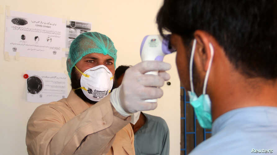 A health worker takes the temperature of a man who returned from Iran and is under medical observation, after Pakistan sealed…