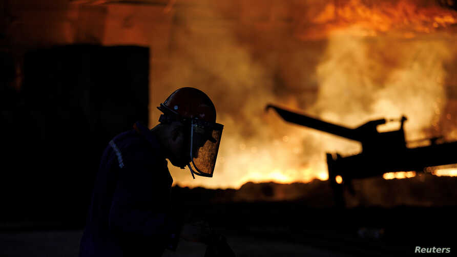 FILE PHOTO: A worker is silhouetted against a blast furnace at the Chongqing Iron and Steel plant in Changshou, Chongqing,…