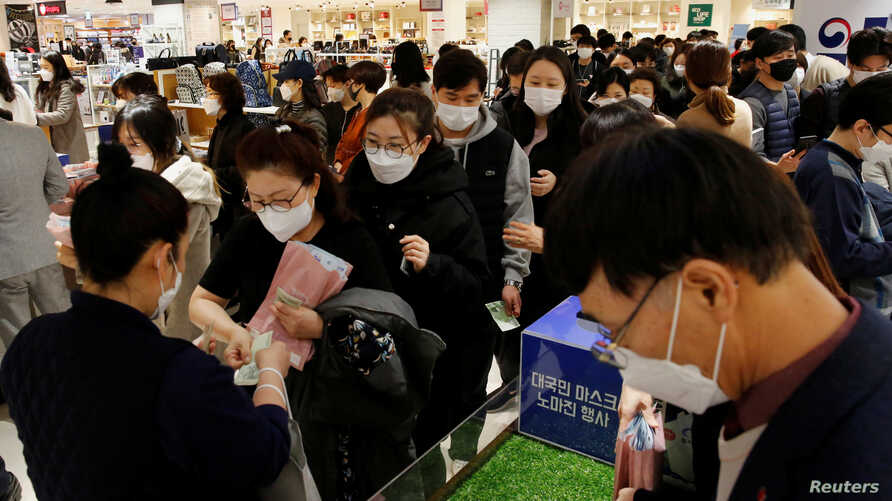 People wearing masks to prevent contracting the coronavirus wait in line to buy masks at a department store in Seoul, South…