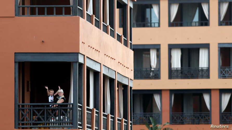 A woman plays with a child on the hotel terrace in H10 Costa Adeje Palace, which is on lockdown after novel coronavirus has…