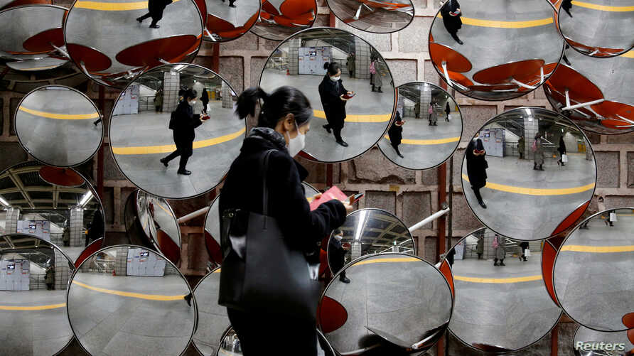 FILE PHOTO: A woman wearing a mask to prevent the coronavirus is reflected in the mirrors, in Seoul, South Korea, February 24,…