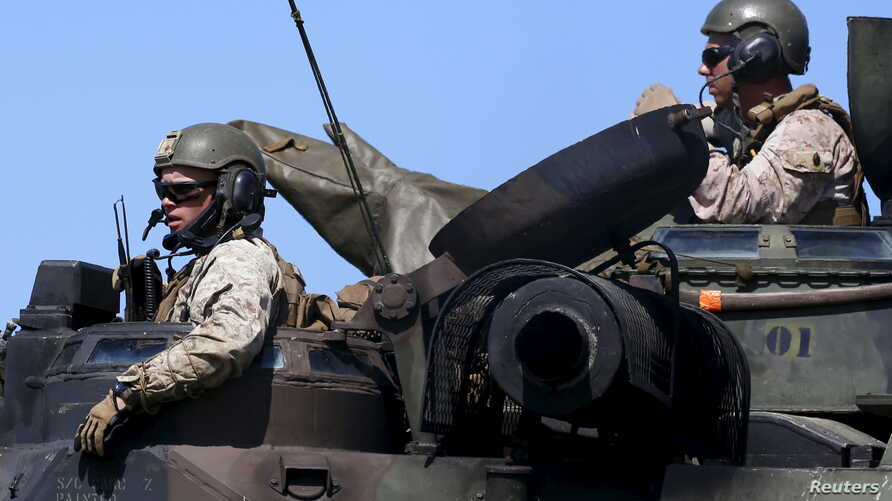 U.S. Marines from the 3rd Marine Expeditionary Brigade sit atop an amphibious assault vehicle during assault exercises with…