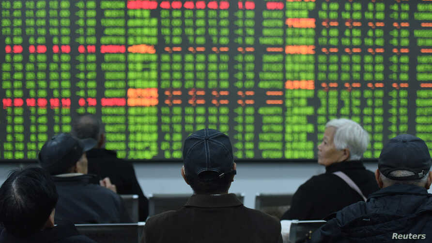 Investors sit in front of a board showing stock information at a brokerage house on the first day of trade in China since the…