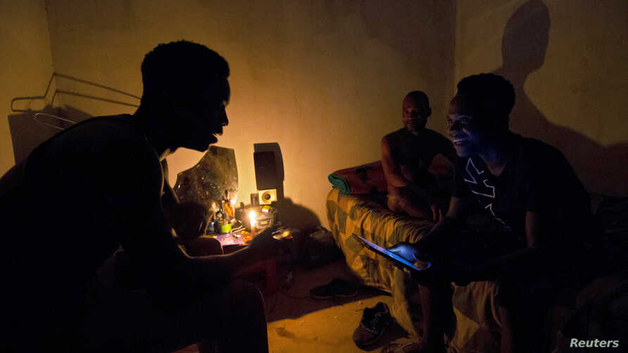 FILE PHOTO: Friends talk by candle light during load shedding in Embo, South Africa March 18, 2019. REUTERS/Rogan Ward/File…