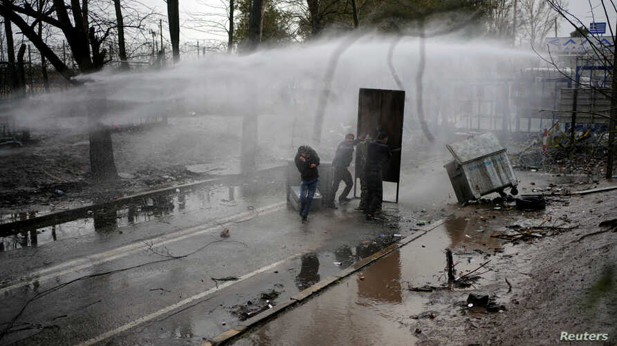 Greek riot police use a water cannon to disperse migrants as they wait on the no man's land between Turkey and Greece, at…
