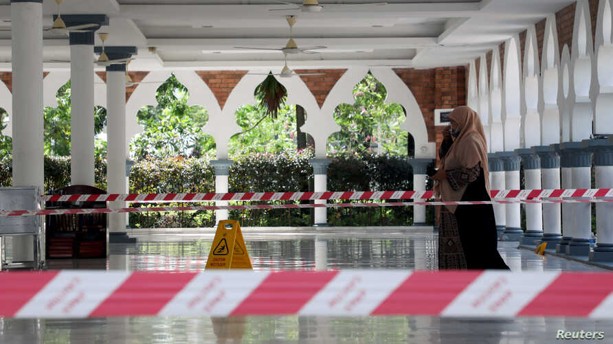 A woman wearing a protective mask walks at a mosque following the outbreak of coronavirus, in Kuala Lumpur, Malaysia March 16,…