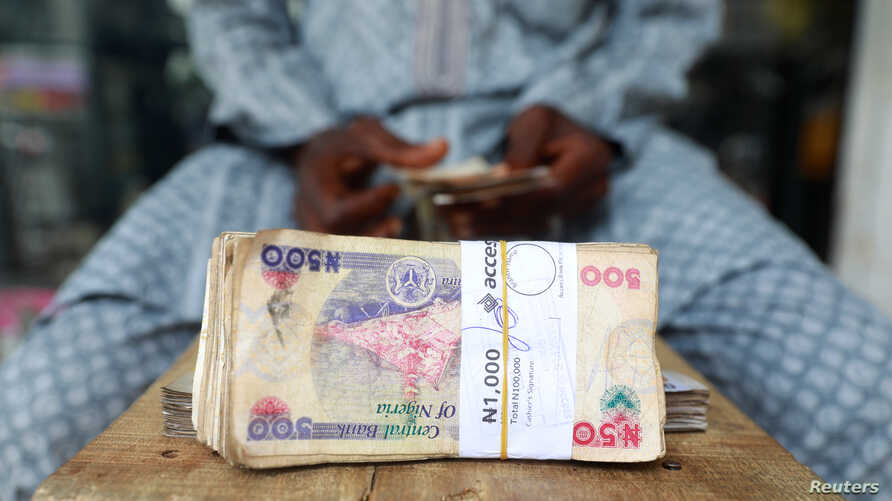 A money changer counts Nigerian currency notes for a customer in Nigeria's commercial capital, Lagos, Nigeria March 16, 2020…
