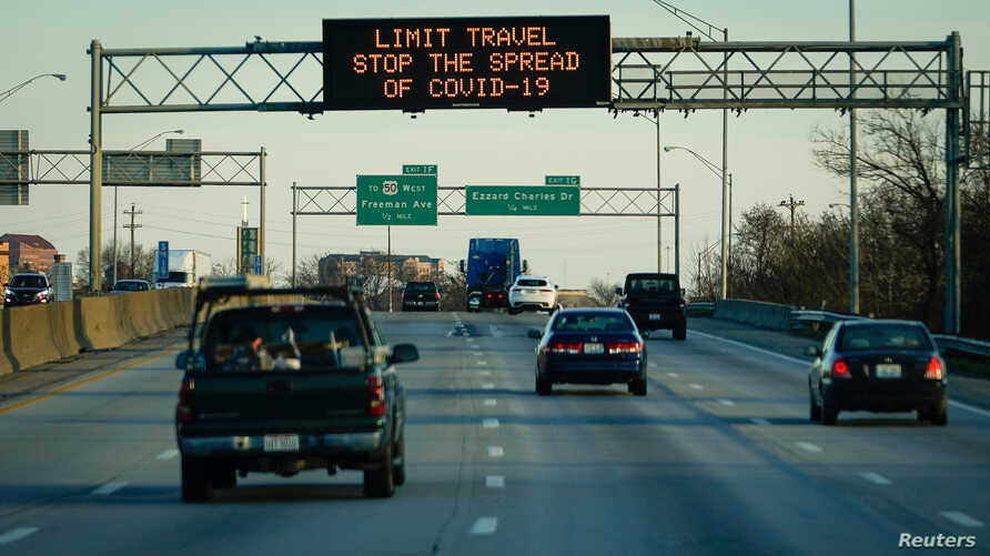 A highway sign on Interstate 75 advises travelers to limit travel in order to slow the spread of the novel coronavirus (COVID…