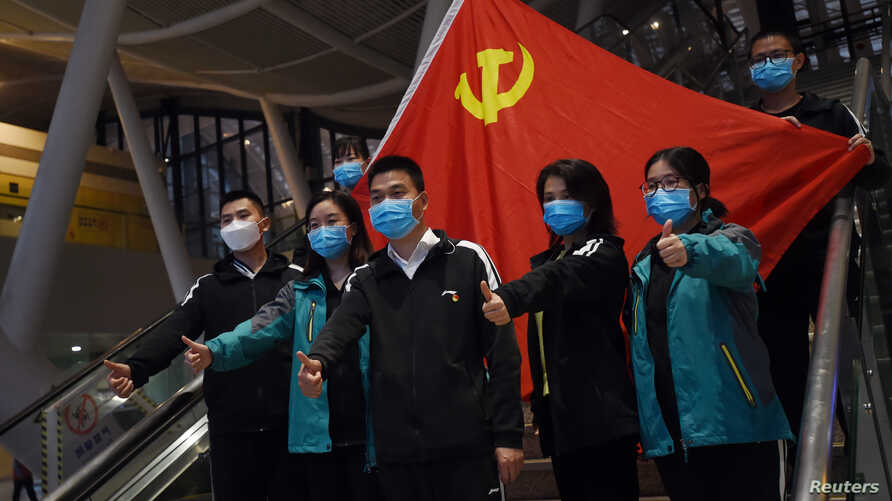 Medical workers from outside Wuhan pose for pictures with a Chinese Communist Party flag at the Wuhan Railway Station before…
