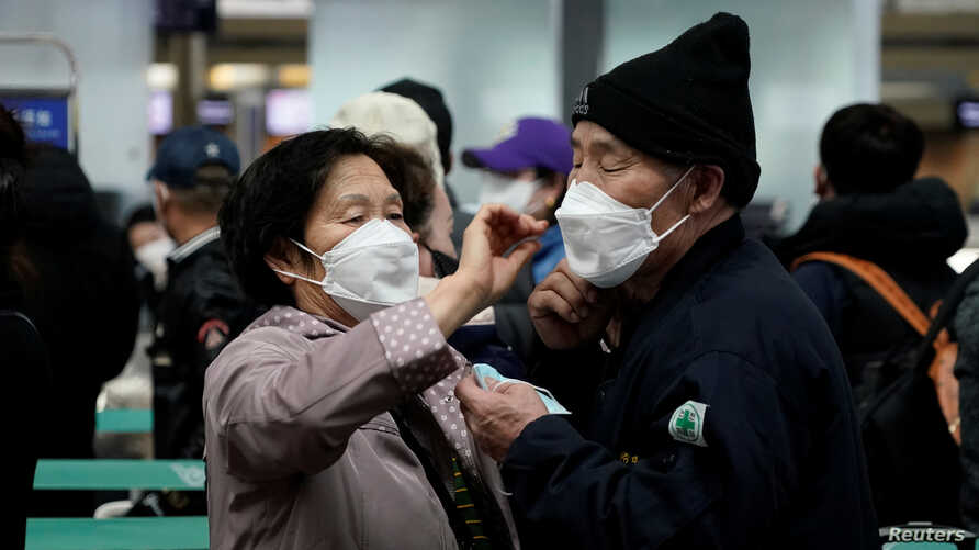 A woman wearing a mask to prevent contracting the coronavirus adjusts her husband's mask as they wait to check in at Incheon…