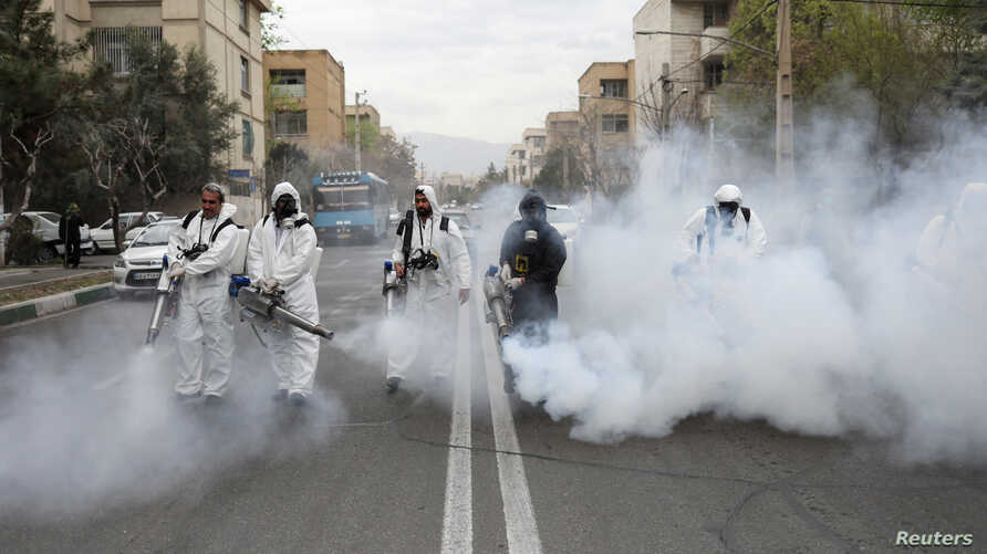 Members of firefighters wear protective face masks, amid fear of coronavirus disease (COVID-19), as they disinfect the streets,…