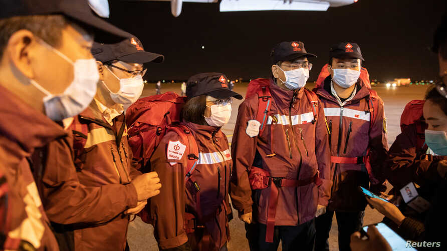 Medical experts from China stand at the Nikola Tesla airport after arriving with medical supplies to help country's fight…