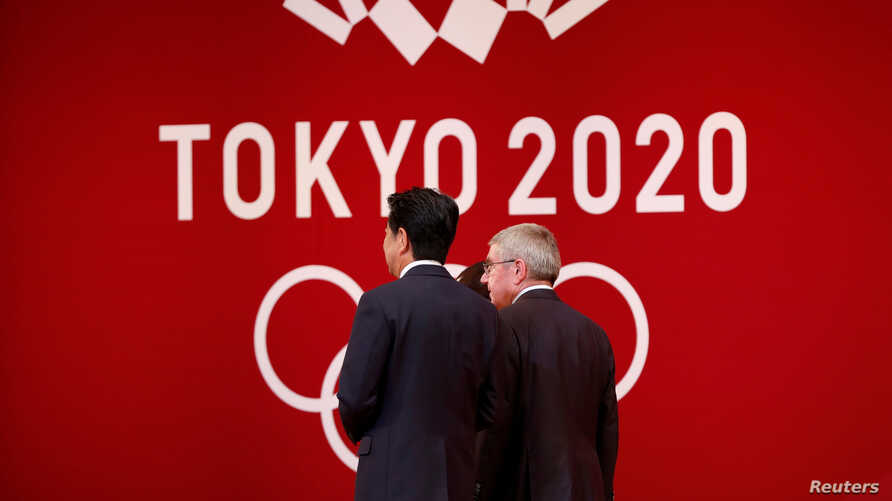 FILE PHOTO : International Olympic Committee (IOC) President Thomas Bach walks with Japan's Prime Minister Shinzo Abe during…