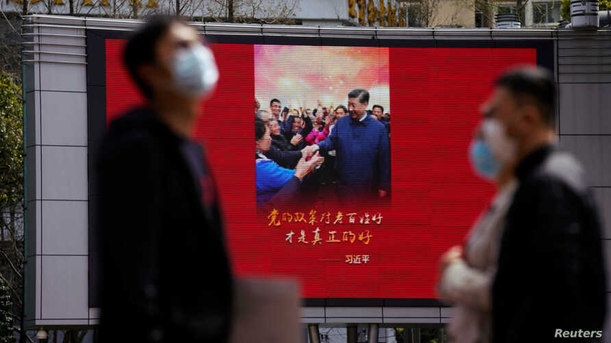 Pedestrians wearing face masks walk past a screen displaying an image of Chinese President Xi Jinping after the city's…