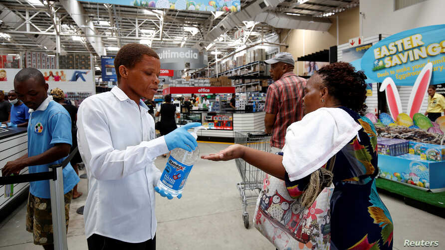 A store assistant gives people hand sanitiser as shoppers stock up on groceries at a Makro Store ahead of a nationwide 21 day…