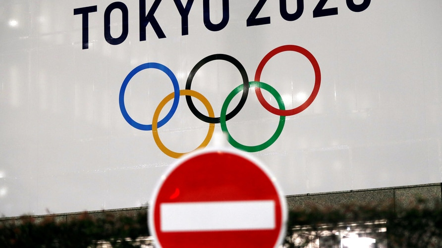 FILE PHOTO: A banner for the upcoming Tokyo 2020 Olympics is seen behind a traffic sign, following an outbreak of the…